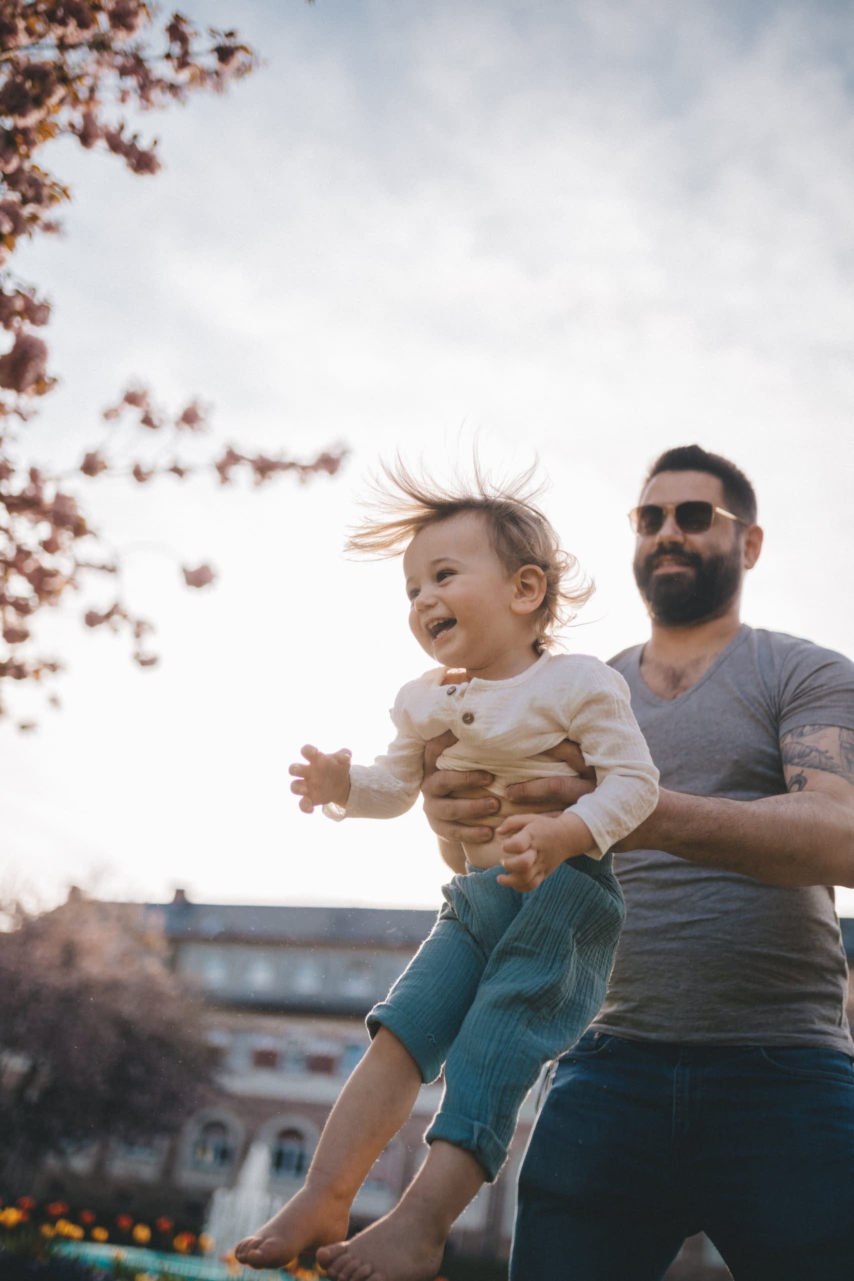 The father throws his child into the air.